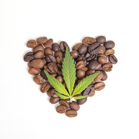 Detail of coffee beans and cannabis concept with marijuana leaf over white background