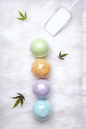 Colorful cannabis bath bombs with marijuana leaves isolated over white background - cannabis spa concept