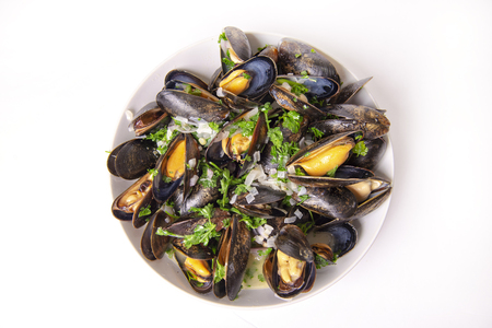Plate of prepared fresh mussels with onion and parsley mignonette isolated over white background