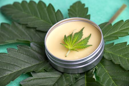 Cannabis salve with hemp and CBD oil and marijuana leaves on green background Stock fotó