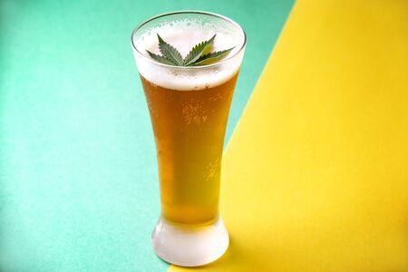 Detail of cold glass of beer with cannabis leaf, marijuana infused beverage concept
