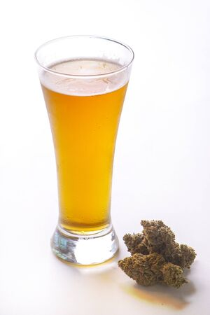 Detail of cold glass of beer with cannabis leaf and nugs isolated over white, marijuana infused beverage concept