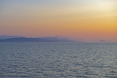 View of the Georgia Strait with the shore of Vancouver Island in the horizon, taken at sunset time in BC, Canada