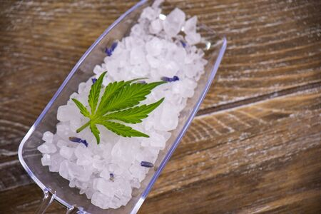 Cannabis infused soaking salts and marijuana leaf - cannabis spa concept
