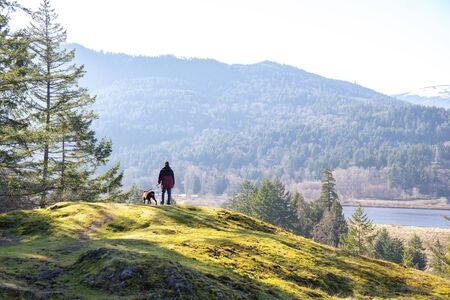 Man and his dog contemplating the view after a hike on Vancouver Island, BC, Canada