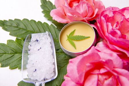 Cannabis infused beauty products with roses, merijuana leaves and CBD salve over white background