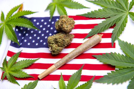 Cannabis leaves, dry nugs and rolled joint over the american flag - veteran theme medical marijuana concept