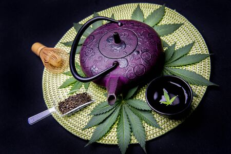 Cannabis infused tea concept with kettle and marijuana leaves isolated on black background
