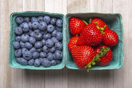 Containers of fresh ripe blueberries and strawberries from the farmers market  Imagens