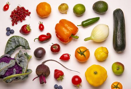 Assorted of fresh fruits and vegetables arranged in a rainbow color pattern over whiate background