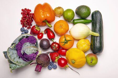 Diverse verse groenten en fruit gerangschikt in een regenboogkleurenpatroon op een witte achtergrond