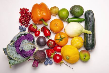 Różne świeże owoce i warzywa ułożone w tęczowy wzór na białym tle