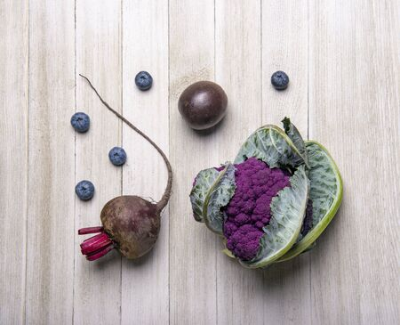 Assortement of purple fruits and vegetables over wood background 写真素材 - 132049100