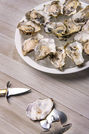 Detail of a plate with fresh shucked oysters from the Canadian west coast over wood background
