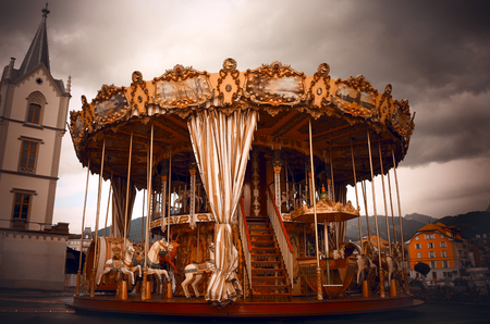 Creepy dark carousel with a cloudy sky background