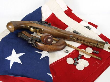 Two antique muzzel loader guns displayed over a US flag. Over a white background.