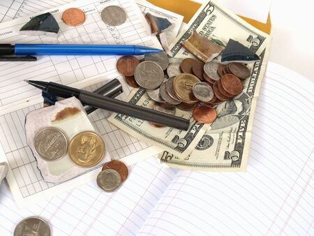 US Currency and broken ceramic pieces from a bank lay over empty ledger books.