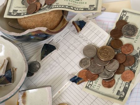 US Currency and broken ceramic pieces from a bank lay over empty ledger books. Stock Photo