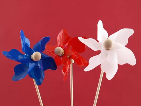 Red, white and blue plastic pin-wheels against a muted red background. Reklamní fotografie