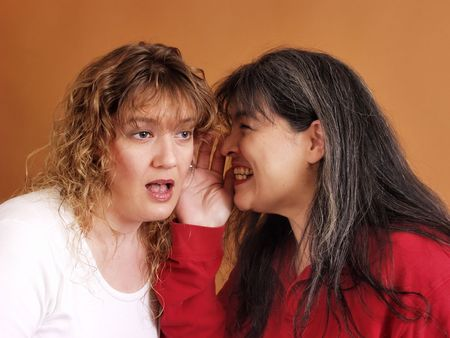 scandalous: A woman whispers something scandalous to a shocked friend Stock Photo