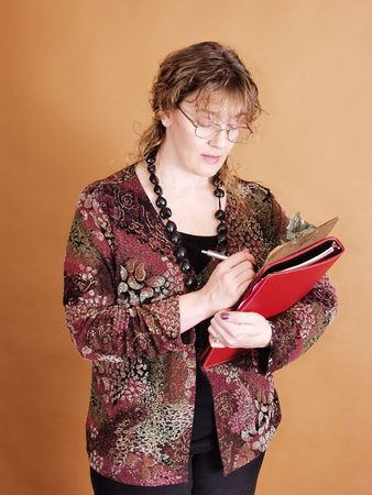 A woman makes a note on her clipboard. On a solid tan background Imagens