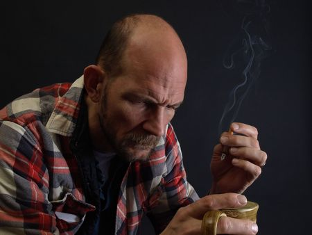 An older man sits, drinking coffee and smoking a cigarette, a contemplative or worried look on his face. Stock Photo
