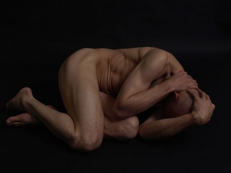 A lean bald male lies on a black background in the fetal position.