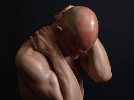 A shirtless bald male adult grips at his head and neck over a black background.