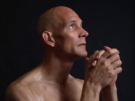 A bald shirtless man clasps his hands in prayer, eyes pleading skyward, over a black background.