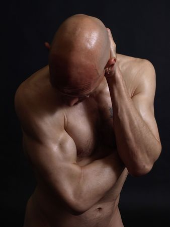 A  bald male holds the back of his head. Over a black background.