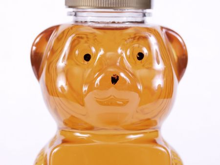 Close view of a bear shaped container full of golden honey. Over a white background.