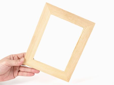 An empty tan frame being held by a hand over a white background. 版權商用圖片