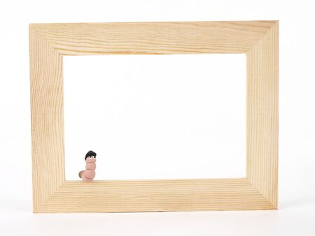 A cute EarthWerm in a bowler hat sits on the edge of a blank tan wood frame over a white background. Photographer holds copyright on figurines.