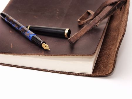 laureate: A leatherbound diary with a pen on an isolated white background.