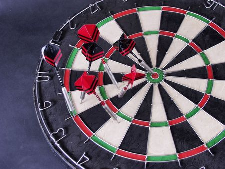 A close-up of steel tipped darts in a dartboard, one with a bullseye Stock Photo