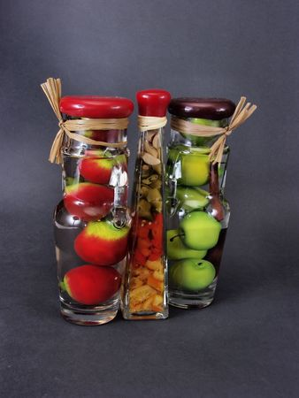 distort: Glass jars filled with green apples, orange citrus, and red pomegranates, on a black background.