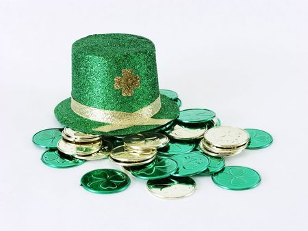 A green St. Patricks Day leprechaun hat and gold and green coins on a white background