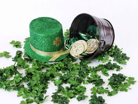 A green St. Patricks Day leprechaun hat next to a metal bucket with coins on a bed of clover, on a white background