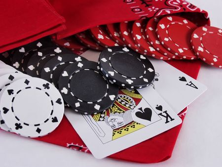 21: Ace and King of Spades tucked up under red white and black poker chips in a red bandana