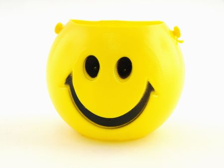 A plastic yellow smiley face bucket isolated on a white background. 스톡 콘텐츠