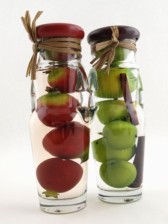Glass jars filled with green apples and red pomegranates, on a white background.