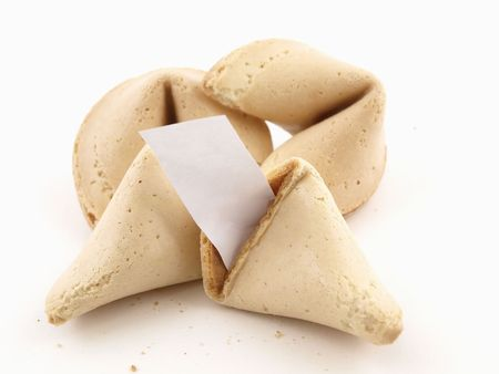 A broken fortune cookie with whole cookies over a white background. Cookie has blank fortune sticking out of one side. photo