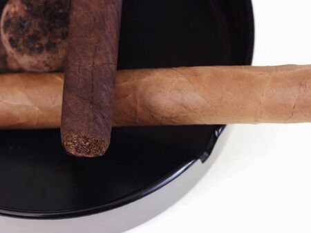 Two unlit cigars resting crossways in an ashtray. Over a white background.