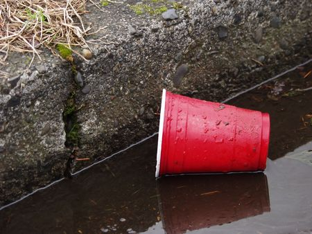 A red plastic cup lays in the gutter, dirty and discarded.