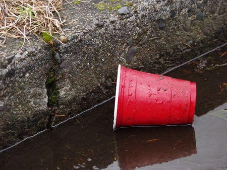 gouttière: Une tasse en plastique rouge fixe dans le caniveau, sales et rejet�s. Banque d'images