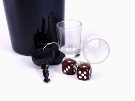 A black bottle with empty shotglasses, dice, and a pair of car keys. Drunk driving, is it worth the gamble? Over a white background.