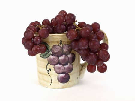 Red seedless grapes draped in a ceramic coffee cup with a grape design on it. Over white.