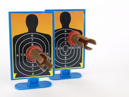 Two target silhouettes with suction cup darts attached to them. Over a white background.