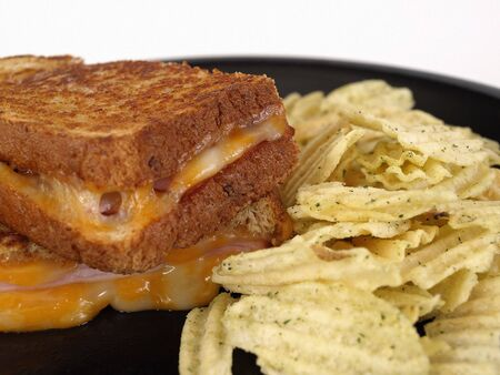 seasoned: Hot maple ham and colby jack grilled cheese sandwich. On a black plate with seasoned potato chips. Stock Photo