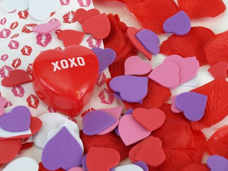 xoxo: A red plastic heart with XOXO surrounded by foam hearts and lipstick  prints. Over white.